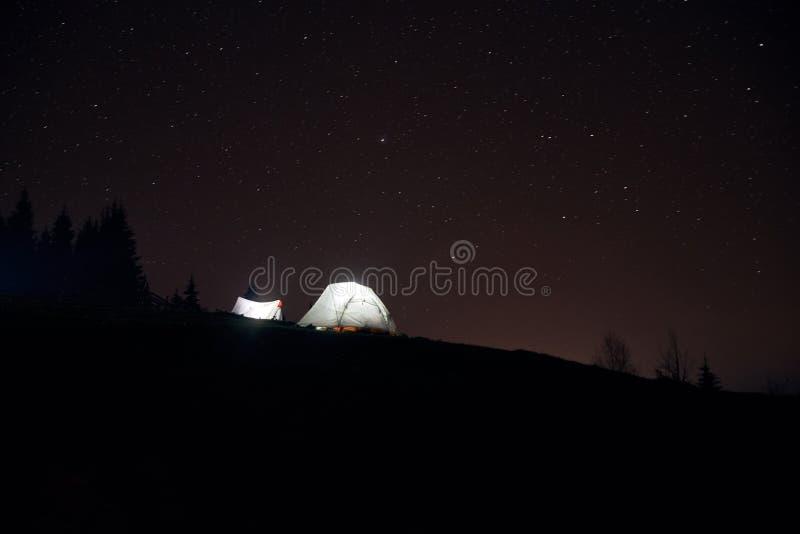 Acampando debajo de las estrellas en la noche en montañas, tiendas iluminadas imágenes de archivo libres de regalías