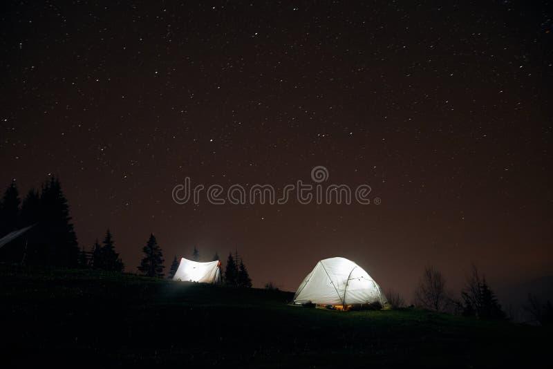 Acampando debajo de las estrellas en la noche en montañas, tiendas iluminadas imagen de archivo