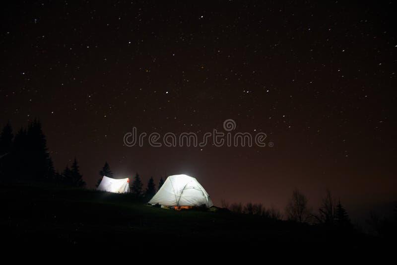 Acampando debajo de las estrellas en la noche en montañas, tiendas iluminadas imagen de archivo libre de regalías