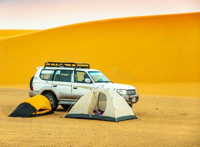 Acampando no deserto sudanês com as duas barracas pequenas, um veículo fora de estrada e uma duna de areia no fundo imagem de stock
