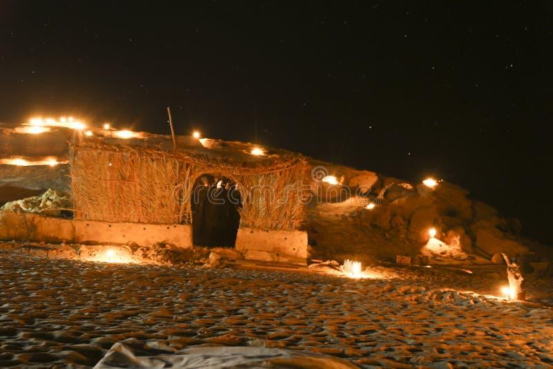 Acampar no deserto sob as estrelas no fogo ilumina-se fotografia de stock