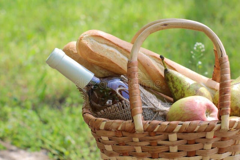 acampar Piquenique na natureza Cesta do piquenique com fruto do vinho e outros produtos na grama verde grossa Resto do ver?o foto de stock royalty free