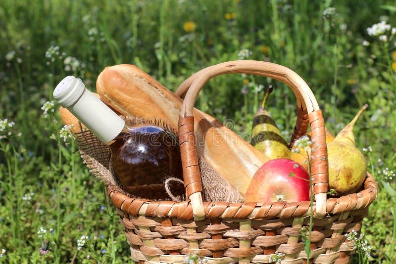 acampar Piquenique na natureza Cesta do piquenique com fruto do vinho e outros produtos na grama verde grossa Resto do ver?o fotografia de stock