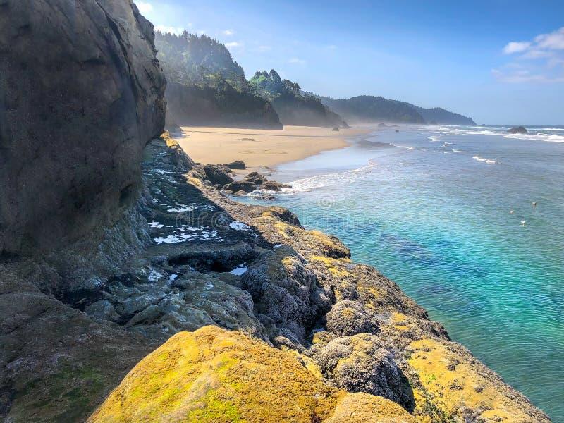 Acantilado en la playa Oregon del punto del abrazo con agua azul del océano del trullo imágenes de archivo libres de regalías
