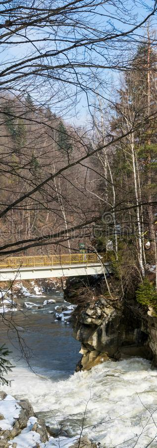 Acantilado sobre corriente y el puente del río de la montaña imagenes de archivo
