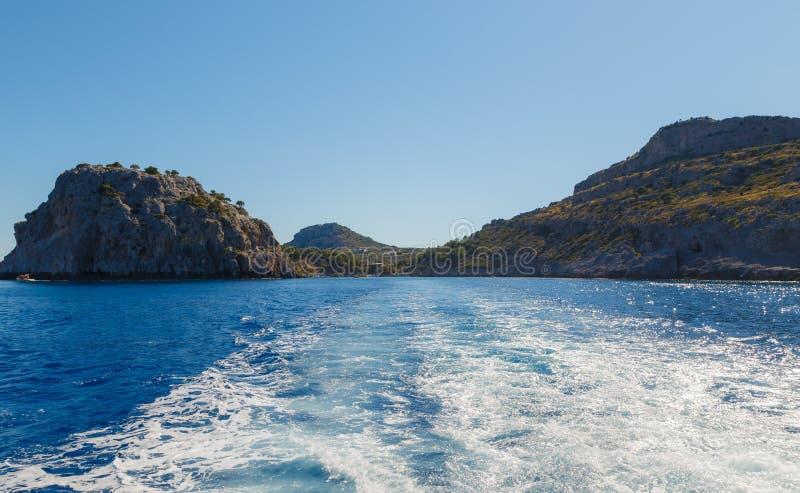 Acantilados costeros Agua de mar azul profunda El mar agita con la espuma y el espray blancos Costa del mar Mediterr?neo Rodas, G fotos de archivo