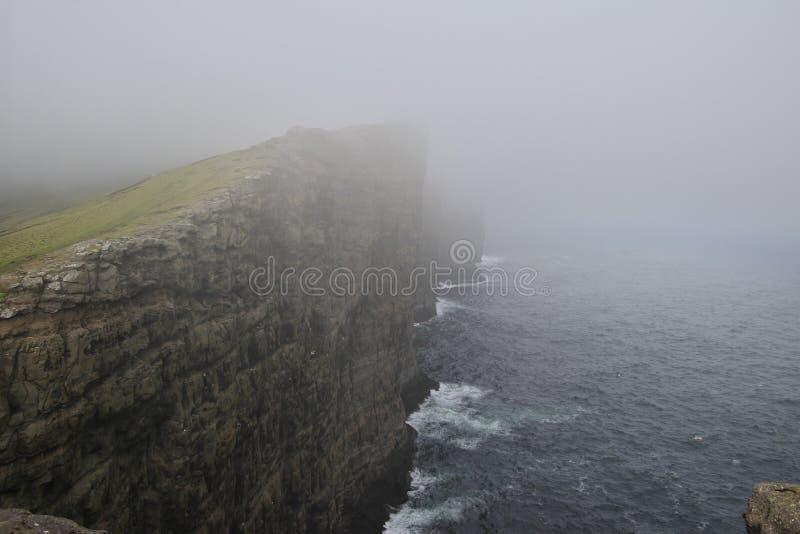 Acantilados cubiertos por la niebla en el lepisosteus del ¡de la isla VÃ de los Faroe Island foto de archivo