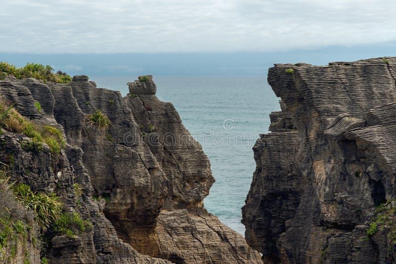 Acantilados en el océano, el agua azul y el cielo nublado, formación de la piedra caliza, paisaje hermoso de Nueva Zelanda fotos de archivo