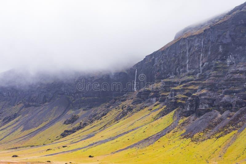 Acantilados en Islandia con las cascadas en las nubes foto de archivo libre de regalías