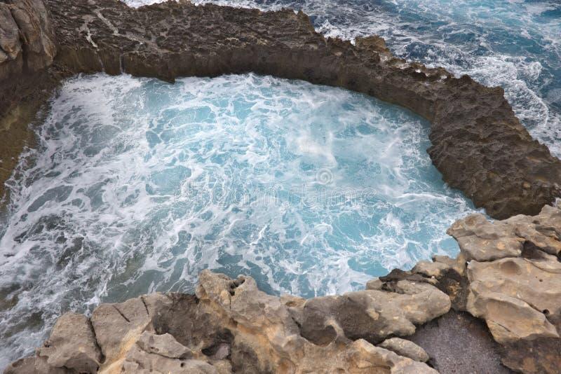 Acantilados rocosos que forman una piscina con agua azul que hace espuma fotografía de archivo libre de regalías