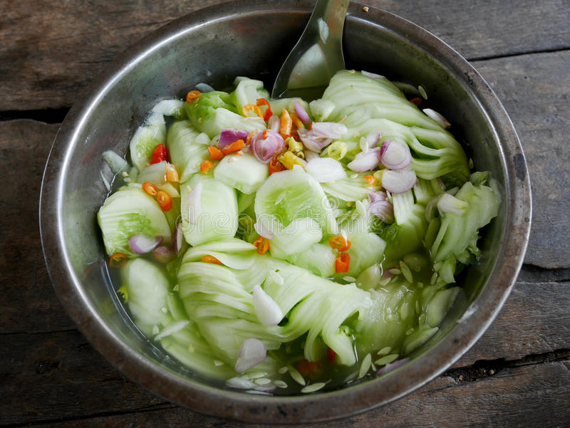 Acar or achat served as a side dish with the thai food. Acar or achat It is made with cucumber, red chilies, red onions or shallots, vinegar, sugar and salt. It royalty free stock photography