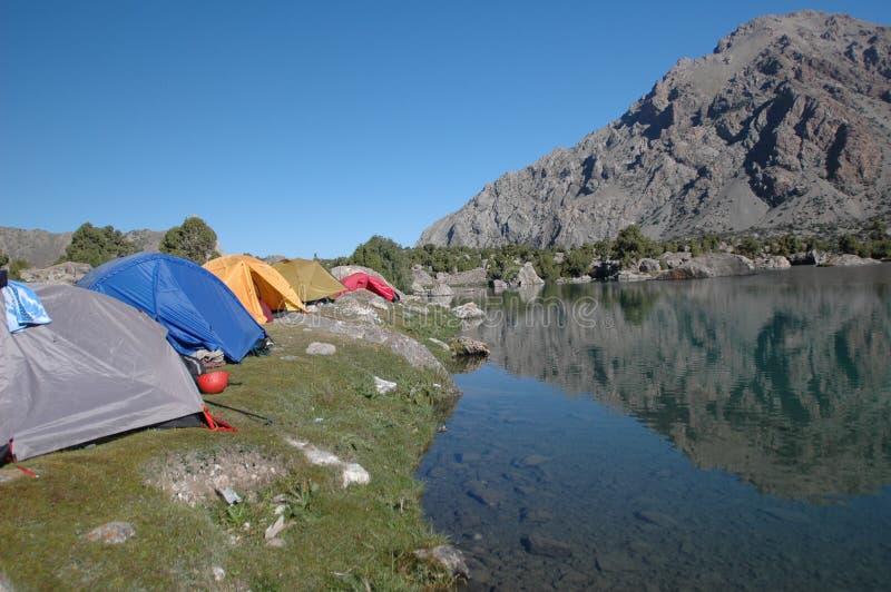 Accampamento basso vicino al lago freddo della montagna immagine stock