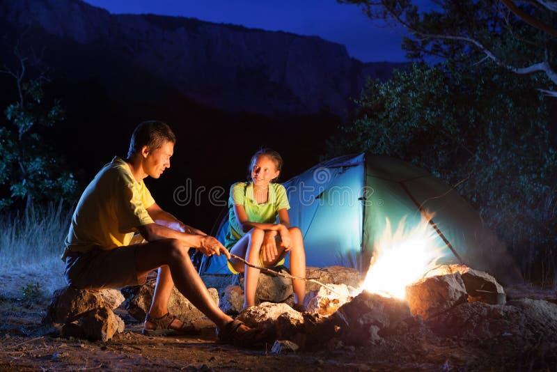 Accampandosi con il fuoco di accampamento alla notte fotografie stock