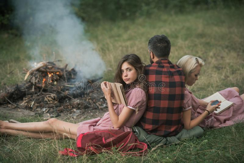 Accampandosi nella regione selvaggia Giri indietro il tipo che esamina il fuoco mentre due belle ragazze leggono il libro, concet fotografie stock libere da diritti