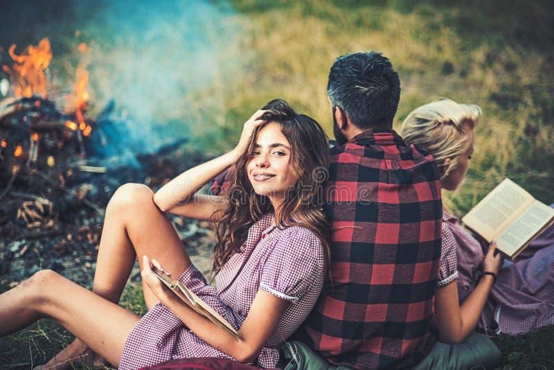Accampandosi nella regione selvaggia Giri indietro il tipo che esamina il fuoco mentre due belle ragazze leggono il libro Sorride fotografia stock libera da diritti