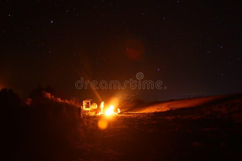 Accampandosi nelle dune di sabbia con un fuoco e le stelle immagini stock