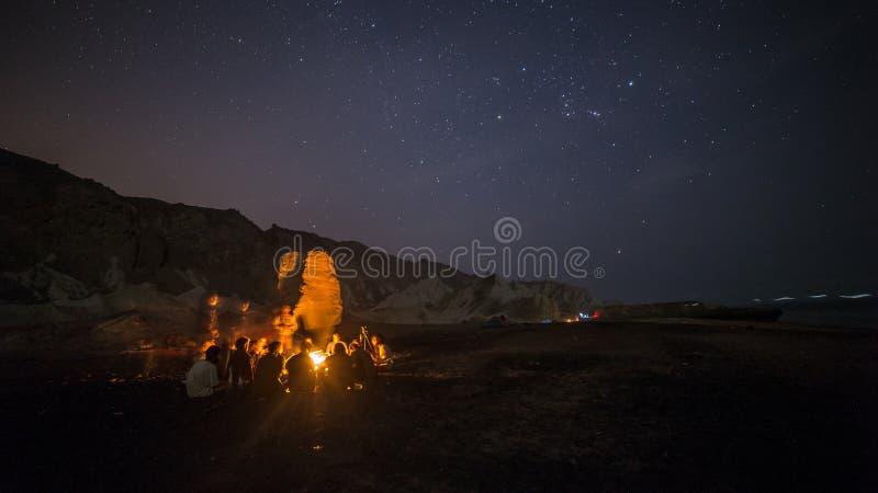 Accampi con fuoco di accampamento nella notte selvaggia del deserto con le stelle immagini stock libere da diritti