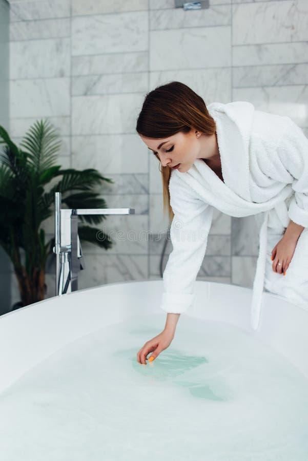 Accappatoio d'uso della donna abbastanza esile che si siede sul bordo della vasca che riempie con acqua immagini stock libere da diritti