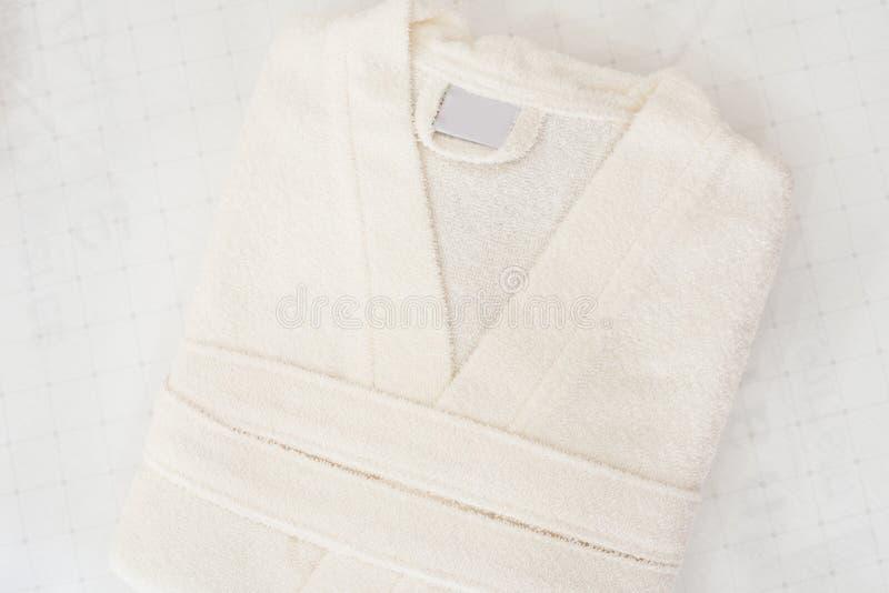 Accappatoio piegato sul letto nella sala Abito bianco immagine stock libera da diritti