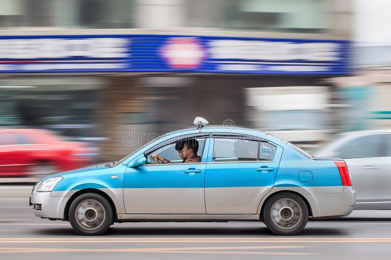 Accelerating taxi with passengers, Dalian, China stock images