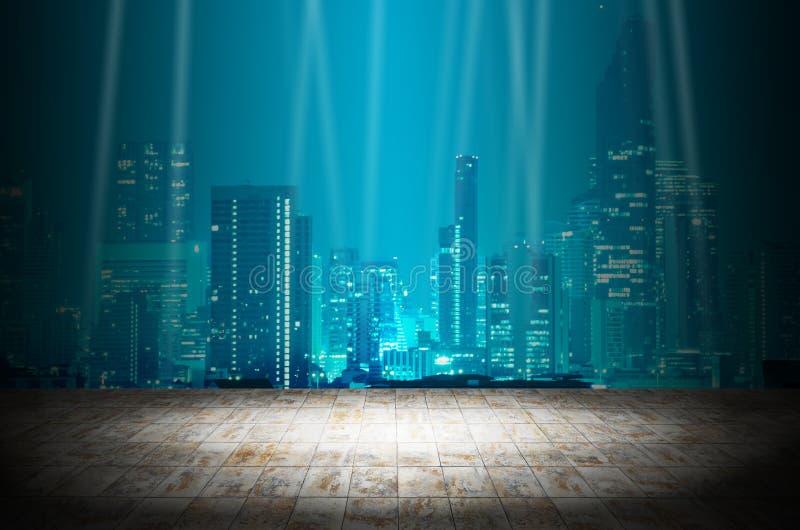Accenda nella stanza scura con il fondo moderno della costruzione della città di notte fotografia stock libera da diritti