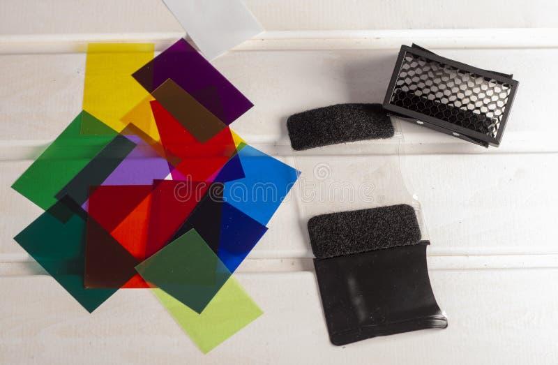 Accendendo i gel del filtro colorato isolati su fondo di legno bianco fotografia stock