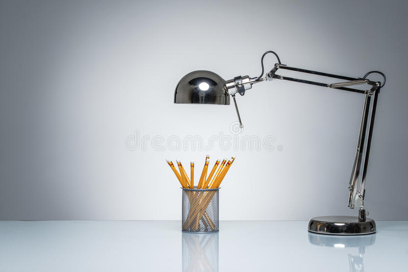 Accendere la cancelleria arancio del supporto della matita con la lampada di scrittorio immagini stock