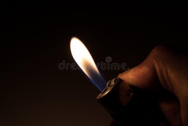 Accendino di gas bruciante della tenuta della mano immagine stock libera da diritti