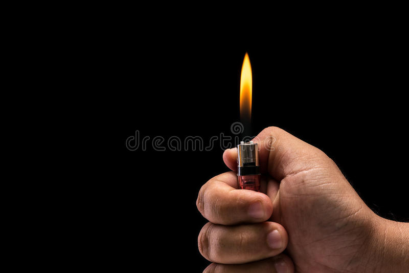 Accendino di gas bruciante della tenuta della mano Colpo dello studio isolato sul nero fotografia stock