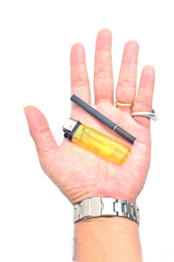 Accendino e sigaretta della tenuta della mano fotografia stock libera da diritti