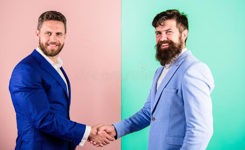 Accept offer. Men in suits businessmen hold hands in handshake. Businessmen with unshaven smiling faces shaking hands stock photos