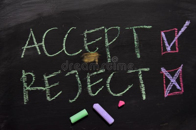 Accept or Reject written with color chalk concept on the blackboard stock photos