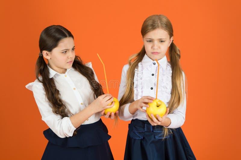 Acceptation d'étudiant de poussée de fruit Fruit frais libre de distribution à l'école Fond orange d'uniforme scolaire d'enfants  photos stock