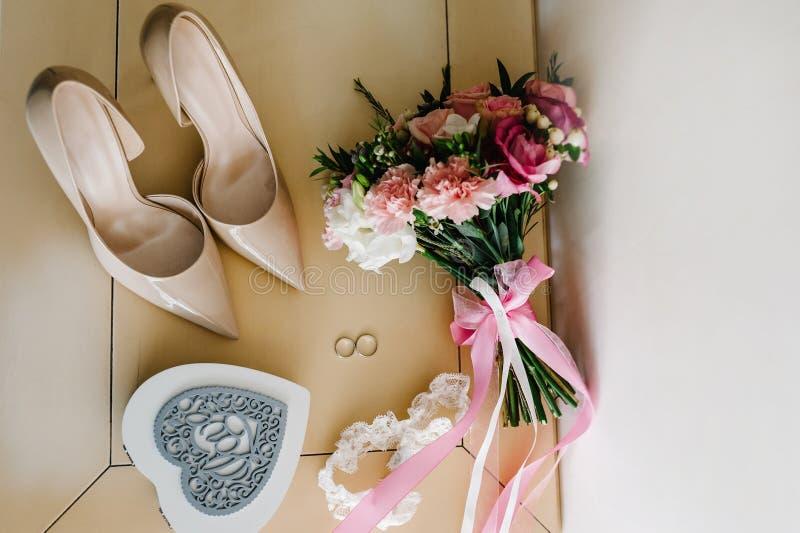 Accesorio de la boda Zapatos clásicos, ` s de la novia del ramo en la tabla en colores pastel imagen de archivo