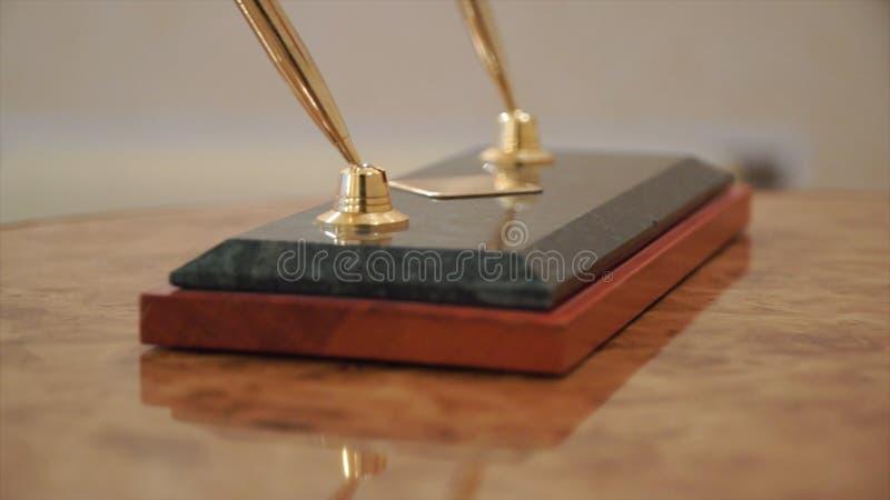 Accesorio del negocio clip Dos plumas y semillas tradicionales de lujo del vintage en una tabla de madera foto de archivo