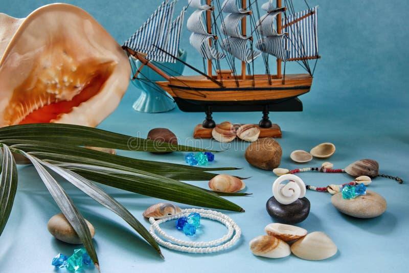 Accesorios, conchas marinas y barco de la playa en un fondo azul imagenes de archivo