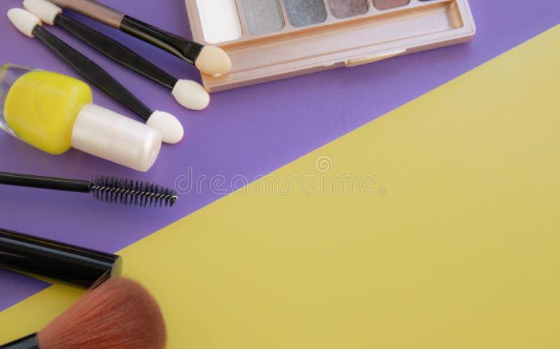 Accesorios cosméticos El cepillo para se ruboriza, cepilla, barniza en un fondo amarillo, púrpura foto de archivo