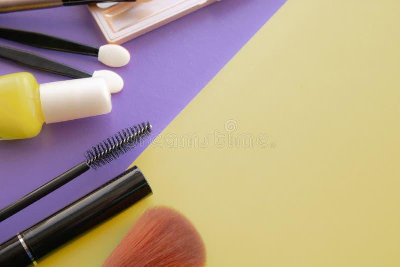 Accesorios cosméticos El cepillo para se ruboriza, cepilla, barniza en un fondo amarillo, púrpura fotografía de archivo libre de regalías