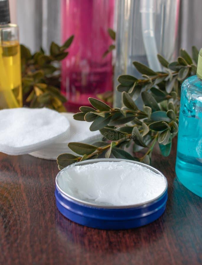 Accesorios cosméticos en un fondo oscuro, crema blanca en un tarro azul fotografía de archivo