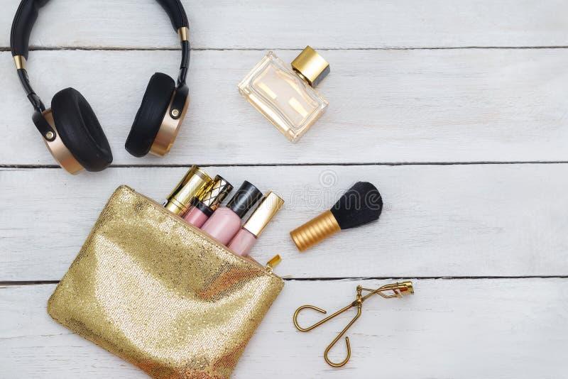Accesorios, cosméticos, mentira brillante de los auriculares en un backgro de madera imagen de archivo