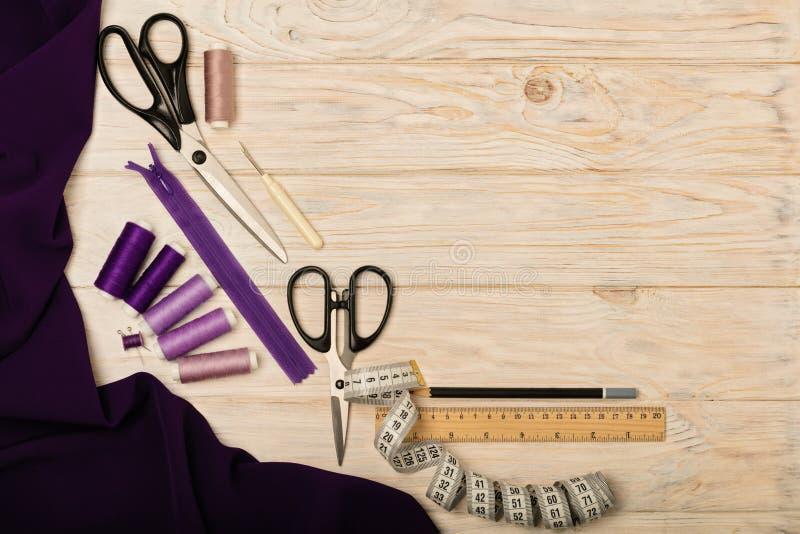 Accesorios de costura en un fondo de madera ligero de la púrpura y del li imagenes de archivo