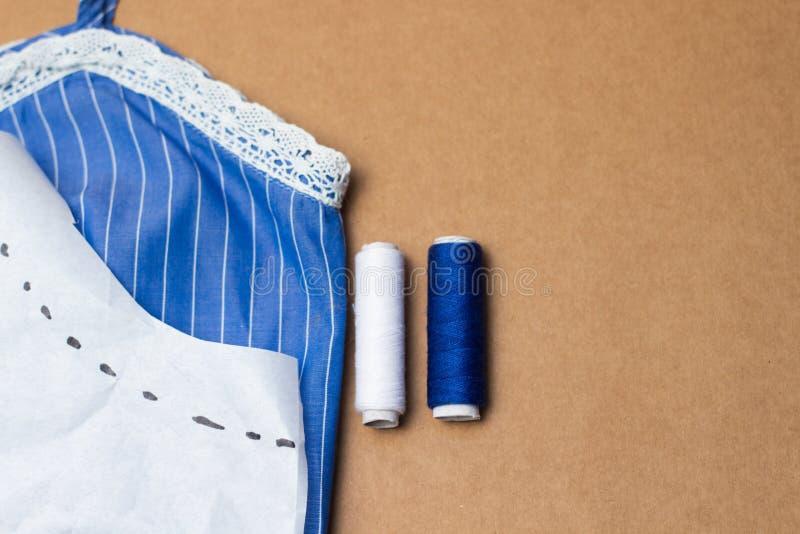 Accesorios de costura, pedazo de tela azul con el cordón, cinta métrica e hilo coloreado en fondo del papel de Kraft Para coser e imagen de archivo