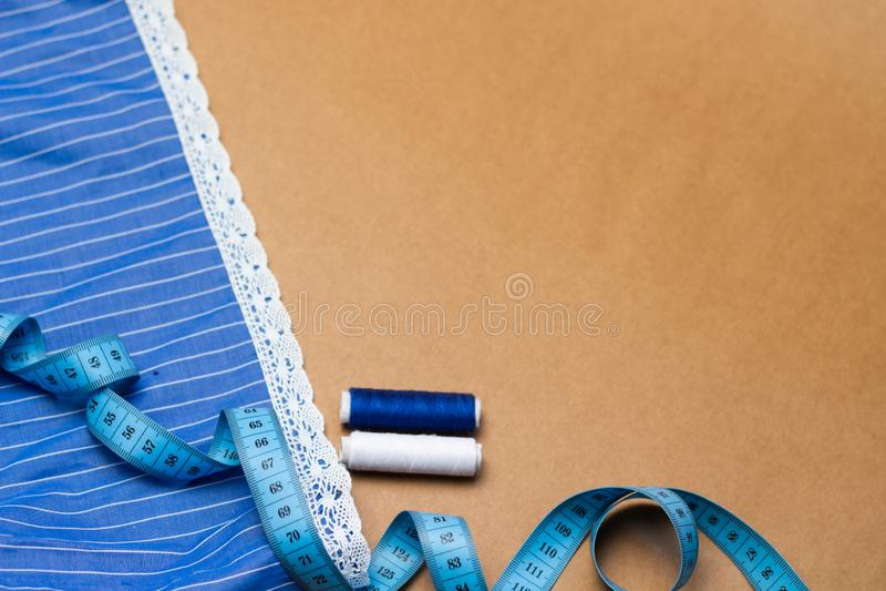 Accesorios de costura, pedazo de tela azul con el cordón, cinta métrica e hilo coloreado en fondo del papel de Kraft Para coser e foto de archivo