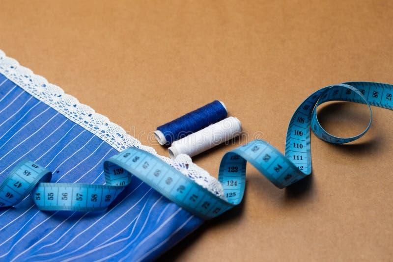 Accesorios de costura, pedazo de tela azul con el cordón, cinta métrica e hilo coloreado en fondo del papel de Kraft Para coser e imagen de archivo libre de regalías