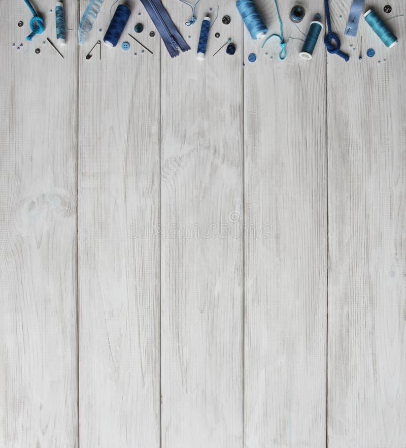 Accesorios de costura y accesorios para el color azul de la costura Carretes del hilo, pernos, botones, cintas en fondo de los ta imagenes de archivo