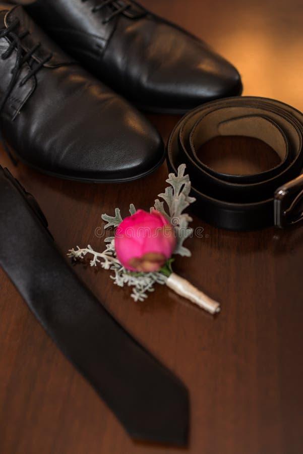 Accesorios de Groom's: una pieza de zapatos negros en el foco, boutonniere de la flor, correa de cuero, corbata fotos de archivo libres de regalías