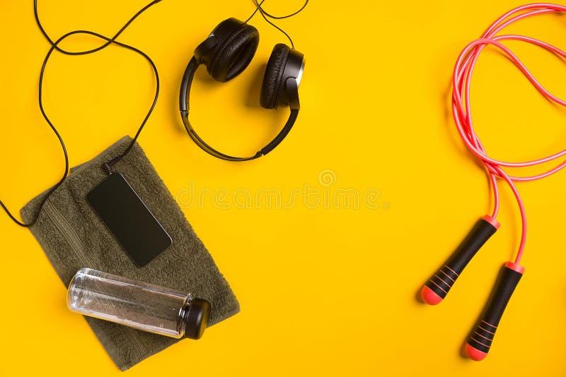 Accesorios de la aptitud en un fondo amarillo cuerda que salta, botella de agua, toalla y auriculares foto de archivo