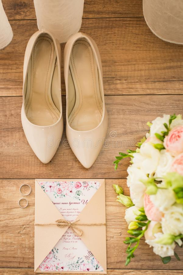 Accesorios de la boda: zapatos nupciales, anillos, invitación, anillos Detalles de la boda en sombras beige Visión desde arriba imagen de archivo libre de regalías