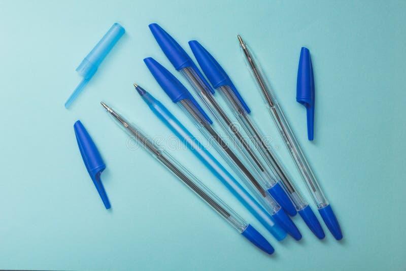 Accesorios de la escuela, plumas azules en un fondo azul imagenes de archivo