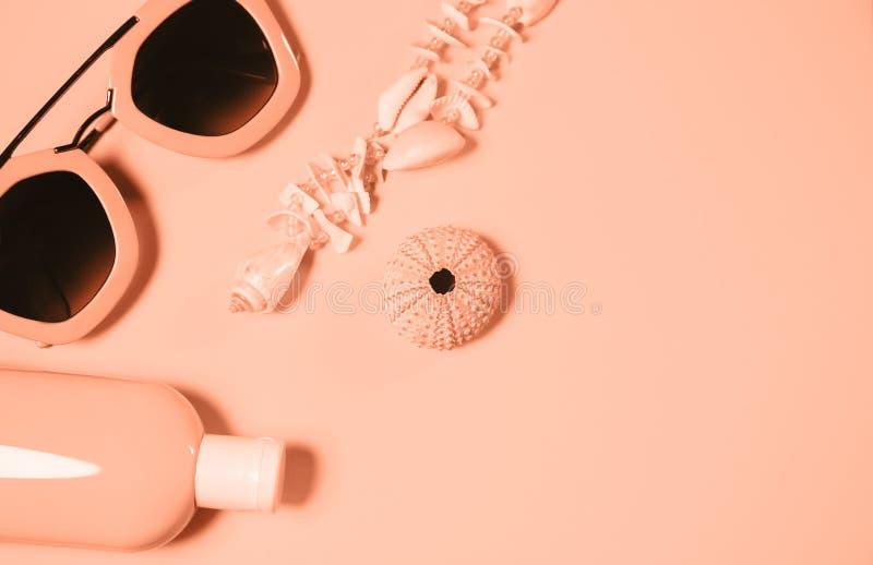 Accesorios de la playa en un fondo colorido Cáscara del erizo de mar, collar de las cáscaras, una botella de loción de la protecc fotografía de archivo libre de regalías